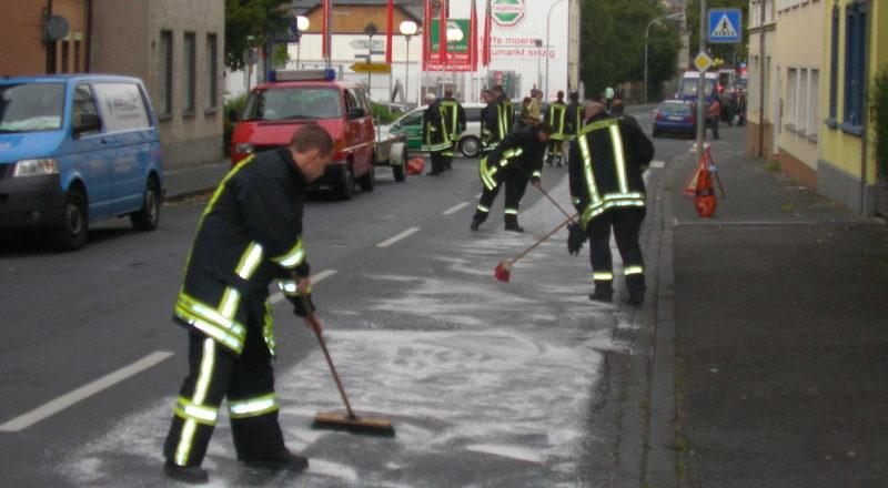 Feuerwehrleute streuen die Fahrbahn ab